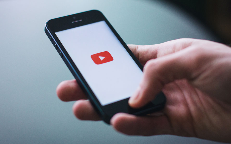 Smartphone mit YouTube-App in Hand